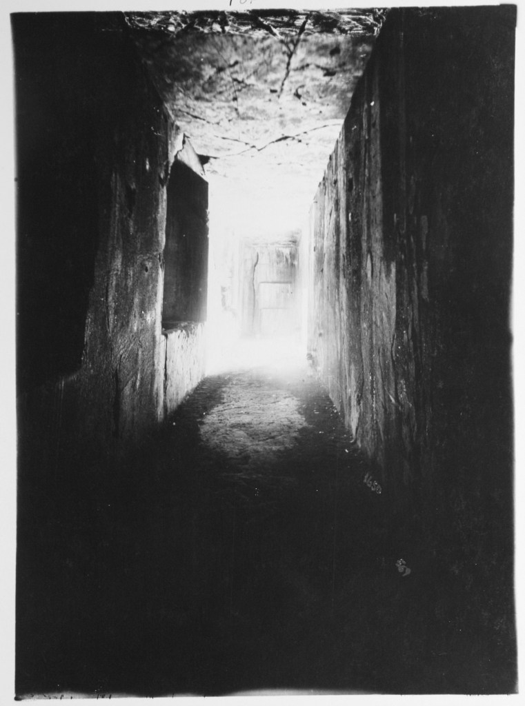 A dark hallway illuminated at the far end enough to highlight the rough, cracked texture of the walls and ceiling of the passage.
