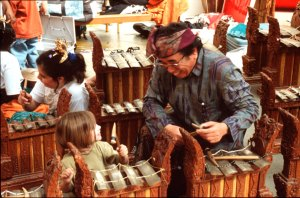Nyoman Sumandhi teaches a young girl to play ugal.