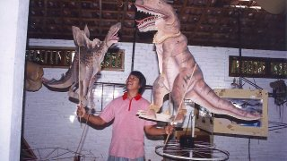 A man holding two large, ornate dinosaurs puppets, a t-rex and stegosaurus.