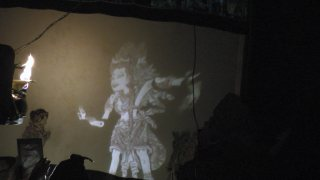 A puppet's figure is projected onto the screen using light and mirrors.