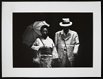 black and white photo of a woman in a kimono holding an umbrella and a man in a fedora and suit