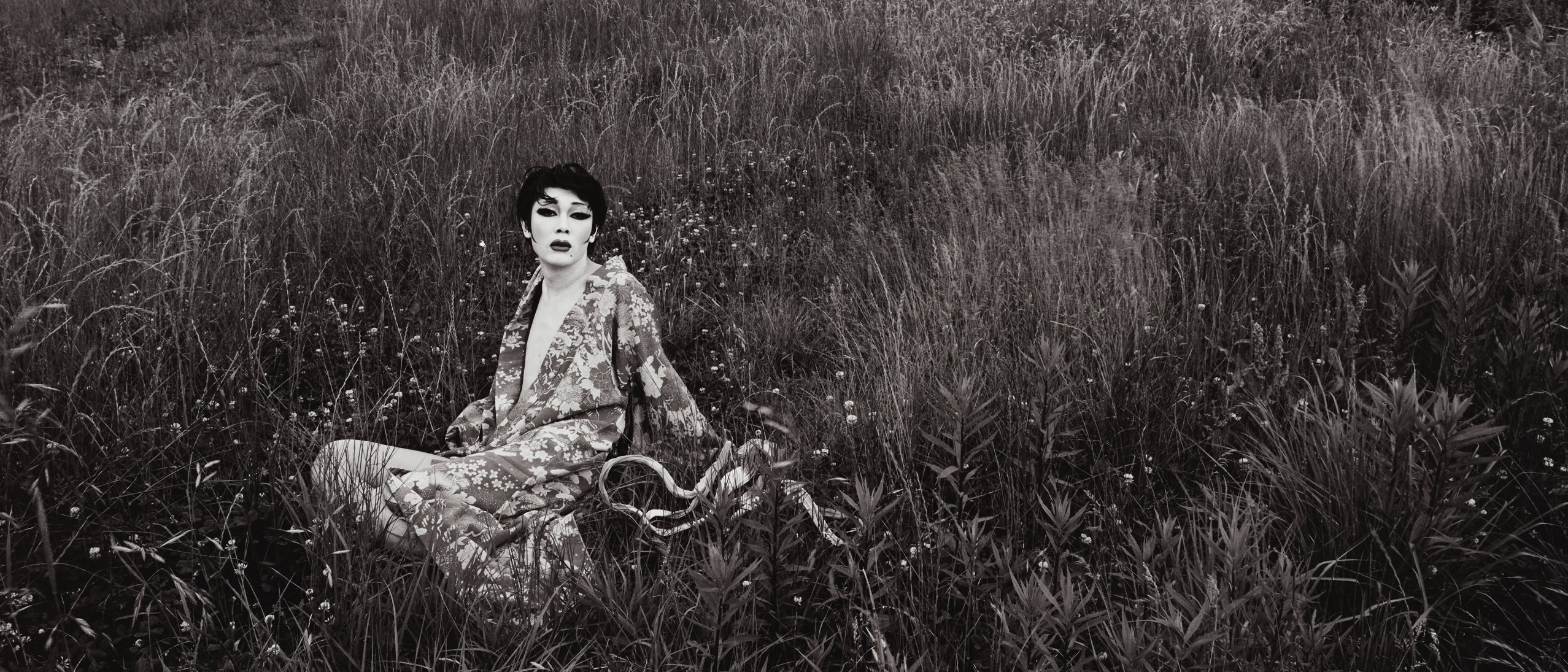 A black and white photo of a lounging figure in makeup and kimono