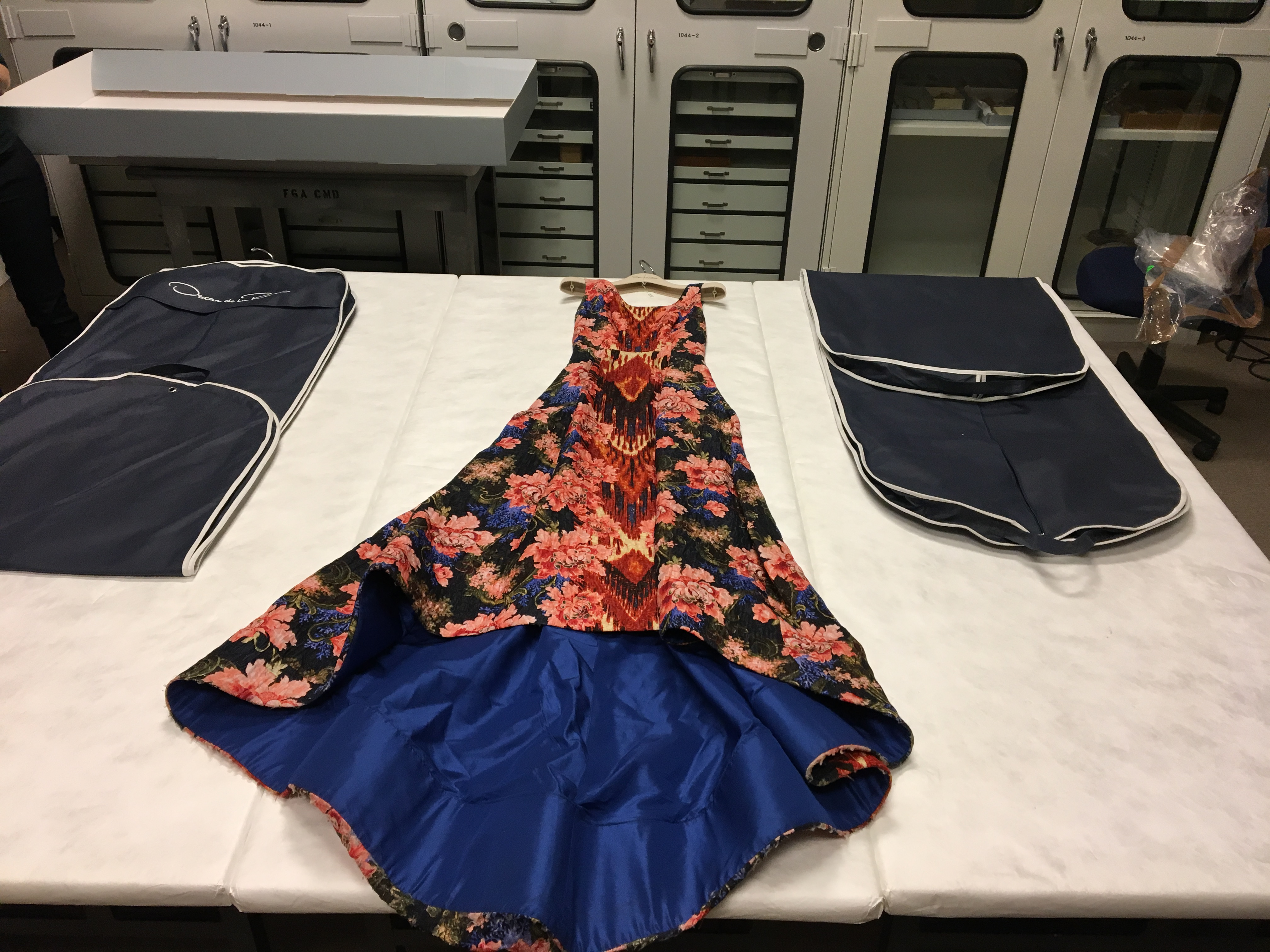 an elaborately floral patterned dress laid out on a table between two navy garment bags