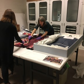 two staff members in purple gloves inspecting the fabric