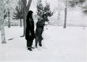 Young boy placing a snow rabbit on top of a snowman.