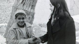 Maura shaking hands with village boy