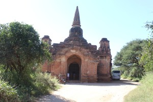 Brick stupa in scrub-forest landscape with people in front
