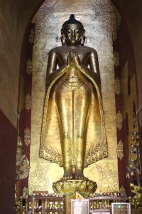 Monumental standing gilt stucco Buddha in a niche