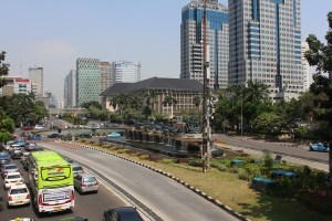 A lawned median dividing a road with cars and a green bus on one side, and tall buildings on the other, with palm trees