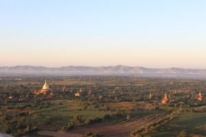 A golden stupa seen from a hot air balloon, among many shrines in a scrub-forest landscape at sunrise, with a river and mountains in the distance