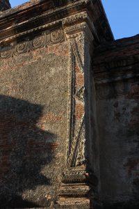 Close up of stucco ornament over brick wall corner