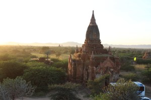 At sunrise, a tall overgrown stupa in the landscape