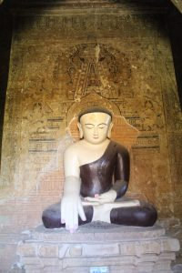Stucco seated Buddha in front of painted Buddha on a wall