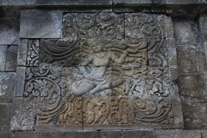 Relief showing flying figure in scrollwork ornament