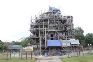 Single-unit temple encased in wooden scaffolding, with construction materials strewn around.