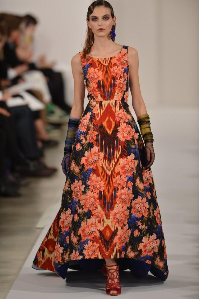 model in vivid floral pattern dress walking down runway
