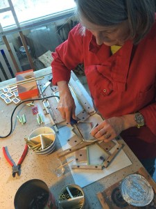 Stained glass artist working on light fixtures