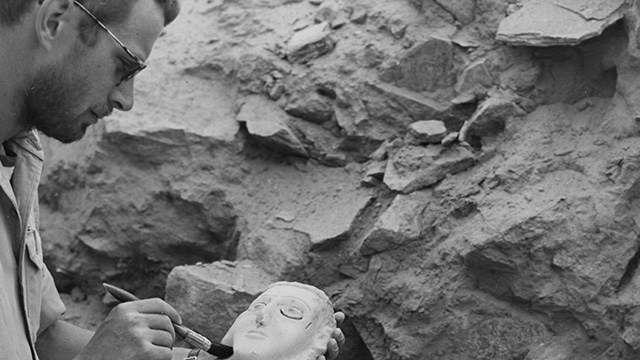 Wendell philips brushing dust from a figure's face.