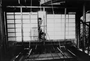 a black and white photo of two children peeking into a room where paper is being made