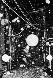 black and white photo of a street scene with power lines and white specs that appear to be snow or rain on the camera lens