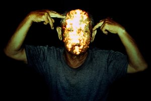 image of a man with light projected on his face and holding his hands to his head