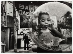 A child blows a huge bubble while a sailor stands in the far background