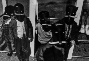 Black and white photo of four children wearing masks