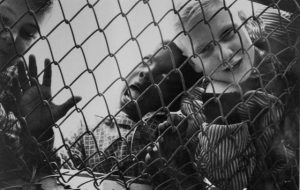 Black and white photo of two children behind a chain link fence