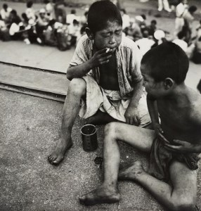 Black and white photo of two children sitting and smoking