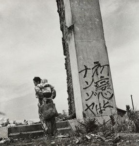 Black and white photo of a mother and child standing by a vertical structure with japanese writing on it