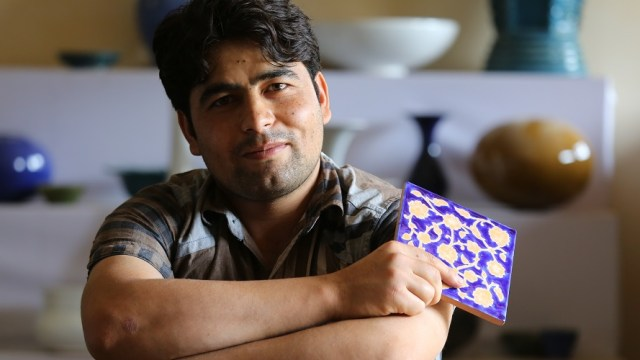 Artist holding a glazed ceramic tile
