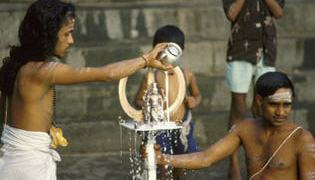 Temple priests ritually bathe in milk a processional image of Shiva's trident.
