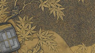 detail from an object depicting an inkstone box against a landscape background in gold.