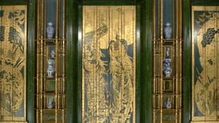 detail of the peacock room shutters, gold detailing against green, with blue and white ceramics displayed on the gold shelving