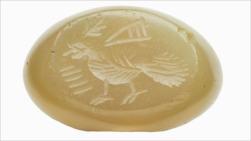 a tan, oval shaped seal carved with the image of a bird. F1993.18.8