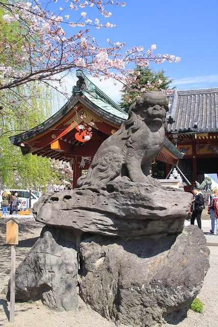Stone statue of a lion-dog (komainu) protecting the shrine against evil spirits