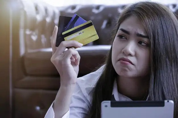 woman with credit cards in hand confused