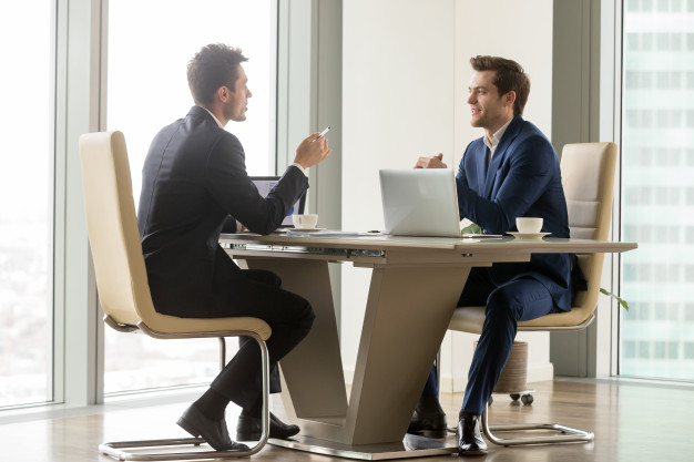 man talking finance to another man at a table