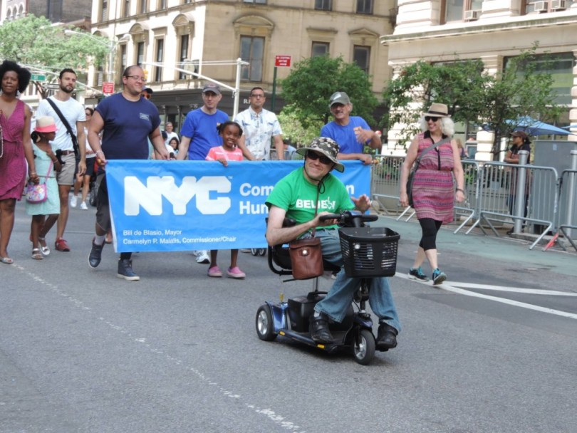A group of marchers carry a blue sign at Disability Pride NYC.