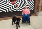 Karin Willison with my service dog sitting in my wheelchair outside in front of a zigzag mural.