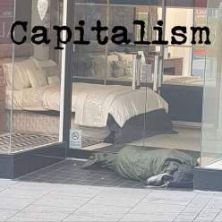 Capitalism Homeless person sleeping outside a glass windowed store showing a bed