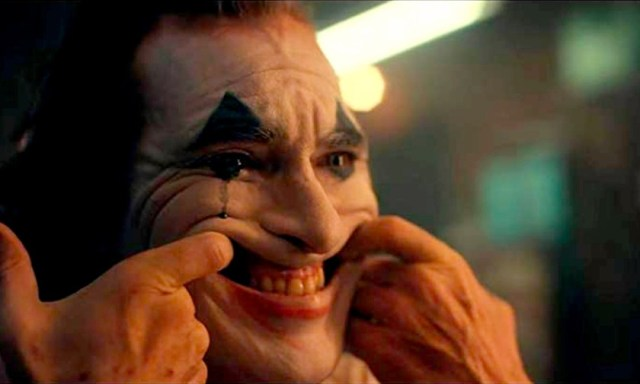 Arthur Fleck forcing a smile while in clown makeup - a single blue tear (Joker 2019)