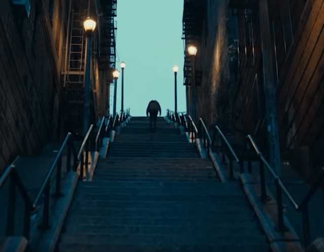 Arthur Fleck trudging up the long and darkened stairs - (Joker 2019)