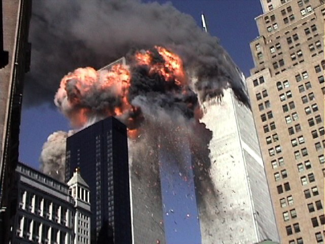 September 11, 2001—Four seconds after Tower 2 gets hit. Flames completely engulf the upper 40 floors of the Towers. At this point I cowered from the fireball's intense radiant heat. Visible are the descending fragments of aluminum fuselages and other debris cast forth by the airplane's impact. (3) Neil deGrasse Tyson