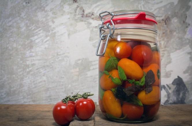 Ein Glas mit fermentierten Tomaten bzw. Paradeiser. Das Glas steht dekorativ auf einer Holzkiste, dahinter ist eine unbehandelte Wand. Auf der Wand ist das Graffiti einer Katze, deren Schwanz der Zeiger einer Uhr ist. Sie wartet darauf das die fermentierten Tomaten fertig werden.