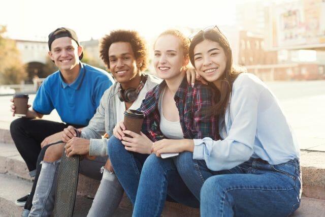 Schüler sitzen auf Mauer