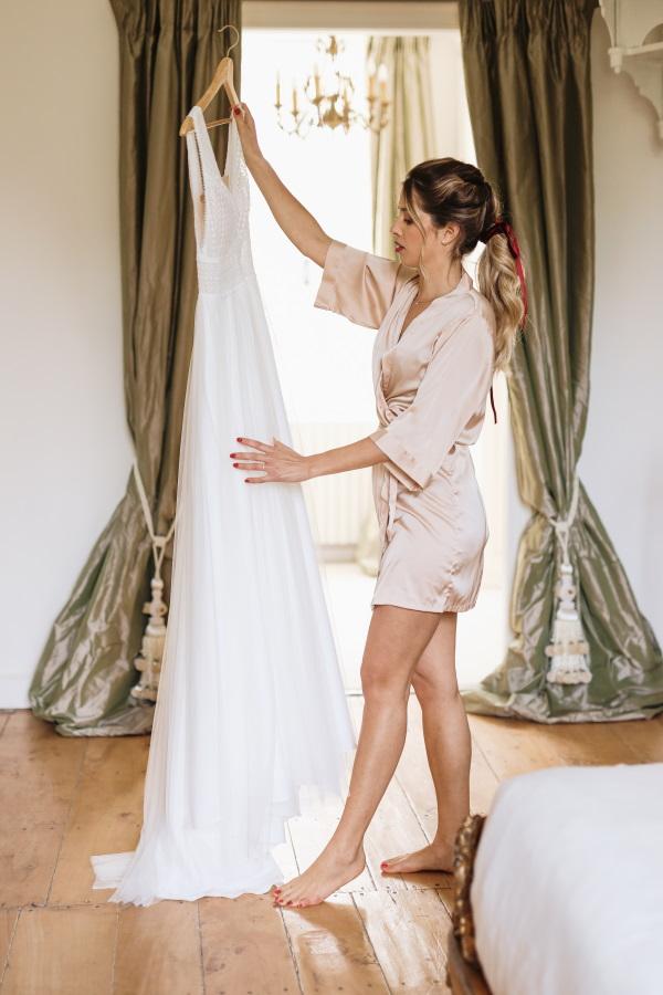 La mariée tient sa robe en l'air sur le cintre portant une robe en soie rose