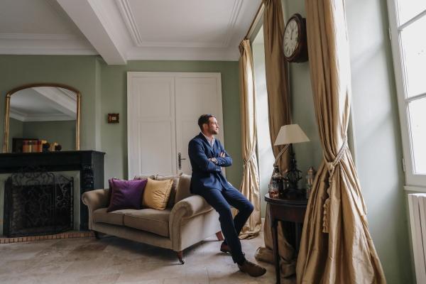 Groom attend avant la cérémonie de mariage dans la chambre aux murs verts du Château Lacanaud assis sur le bras d'un salon