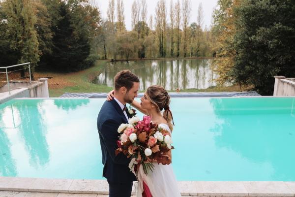 Les mariés se penchent pour un baiser devant la piscine extérieure aquatique