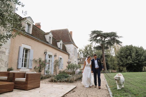 Les mariés à pied avec chien en laisse à travers le jardin à l'extérieur du Château Lacanaud en Dordogne France